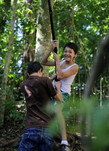 Junior, a 12-year-old Tico, flies through his backyard on a tree swing. His family's backyard includes a series of waterfalls which are used for adventure tours. Sally French/Missouri School of Journalism