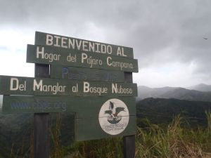 A sign with text in Spanish sits atop a cliff overlooking clouds and mountains.